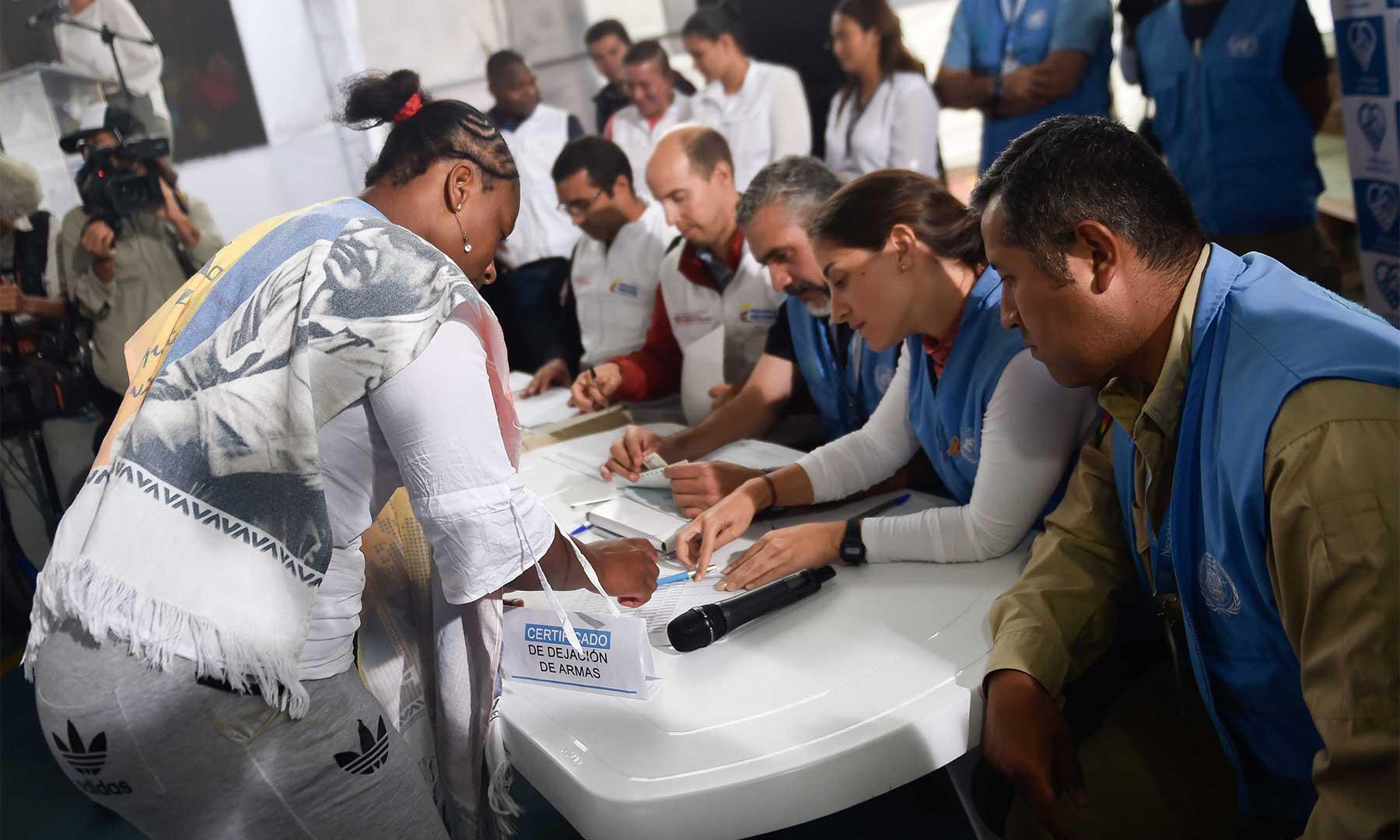 La integrante de las Frac recibe de miembros de la ONU la certificación de entrega de su arma.